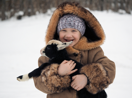 Happy little girl with a newborn lamb in her arms. Winter, cold. Village life in Russia Banque d'images - 115399123