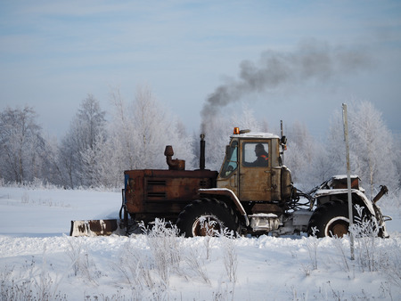 Tver region. Sonkovsky district. Russia. 28 January 2019. Clearing snow from the road. Tractor grader clears snow from the road.