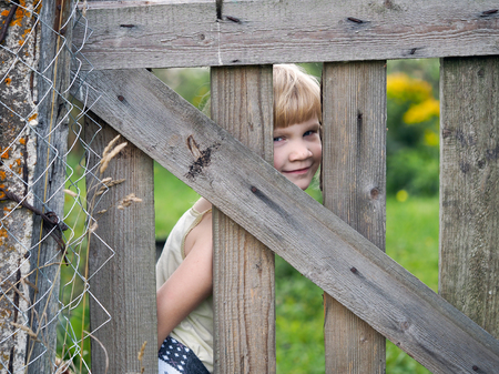 The child looks through the village fence. Portrait of funny little girl