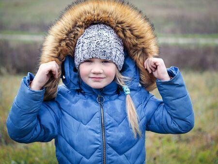 Portrait of a child in a winter jacket in summer. The concept of changing the weather, climate, cold