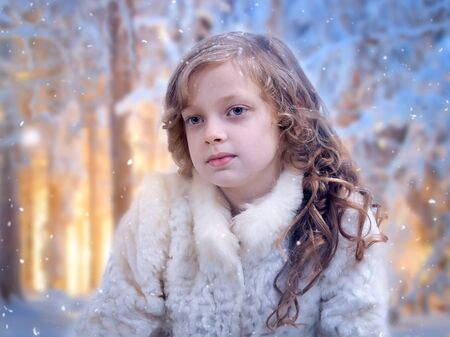 Very beautiful little girl under the falling snow
