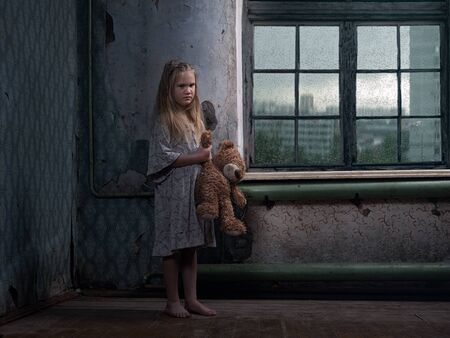 A little girl in a terribly dirty beggar's house. Concept of abandoned children, poverty, harmful habits of parents