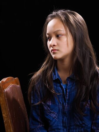 Portrait of a teenage girl on a black background