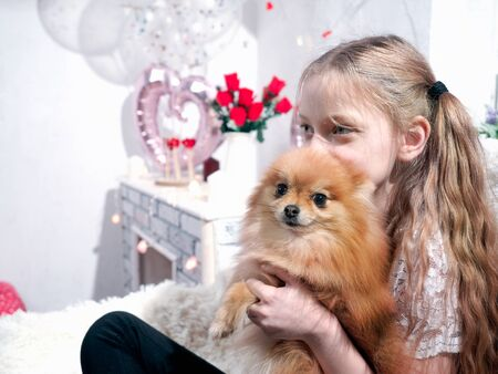 Portrait of a girl with a Pomeranian dog in a holiday lodging