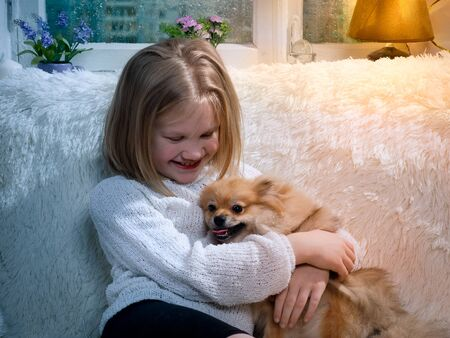 Incredibly happy child with a lap dog 스톡 콘텐츠