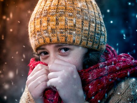 Portrait of a girl under snow in cold weather