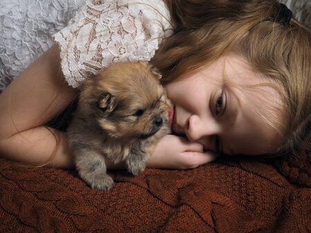 Portrait of a girl with a puppy. The story of a dogs friendship with a child 스톡 콘텐츠