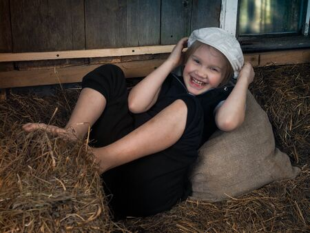 A laughing child in the village in the hayloft. Emotional portrait.