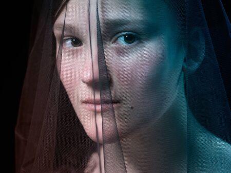 Portrait of a teenage girl under a veil