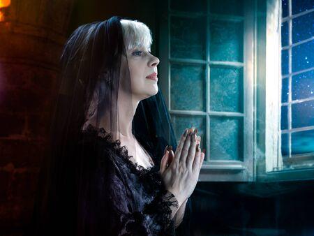 A woman prays. Vintage portrait in a medieval dress