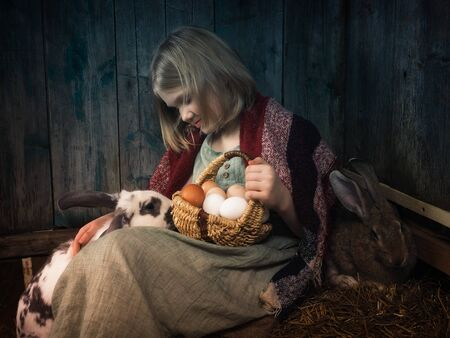 Portrait of a little girl with eggs and rabbits in the village in the hayloft 스톡 콘텐츠