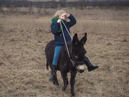 A girl rides a donkey in a field