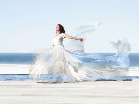 A girl in a flying dress walks along the beach