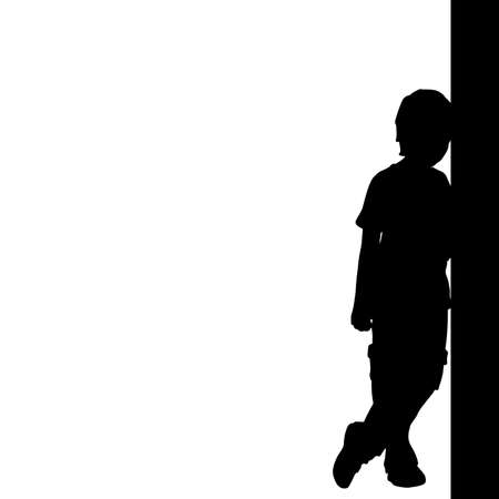 Silhouette of boy standing by the wall.