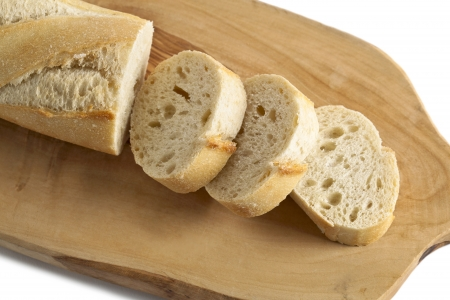 Horizontal and close up image of chopped French bread on a chopping board isolated on Stock Photo - 15378544