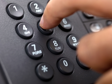 receiver: Close-up cropped image of a person dialing landline phone.