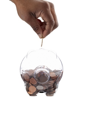 Gold coin inserting on a piggy bank using by the human hand Stock Photo - 15543058