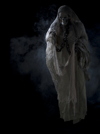 Afbeelding van een menselijk skelet omgeven met rook over donkere achtergrond.