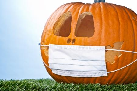 Pumpkin hiding his happy feeling with a medical face mask. Banco de Imagens