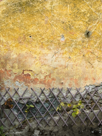 intersecting: Close-up shot of rusted metallic rod on old yellow weathered wall. Stock Photo