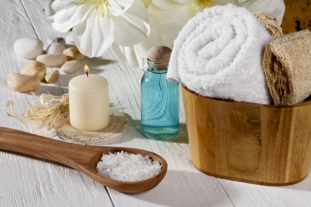 A set of spa products with spa salt on a spoon, towel, oil and a lighted candle on a wooden table Stock Photo - 15543235