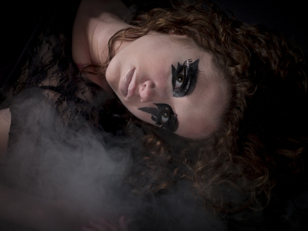 Gothic woman laying in fog photo