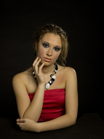 updo: A teen girl wearing a formal dress and an updo on a black background