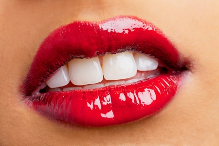 Close-up shot of woman lips wearing red shiny lipstick, Kiran Bahugun