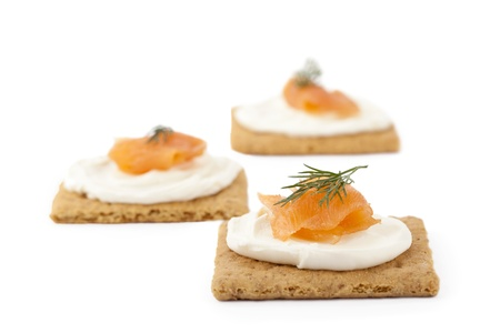 dill leaves: Image of biscuits with smoked salmon and cream cheese top with dill leaves isolated on white