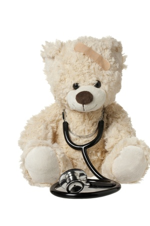 Cute teddy bear with a bandage and stethoscope displayed on white. Stock Photo - 15839372