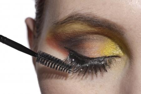 Closeup woman applying eye mascara Stock fotó