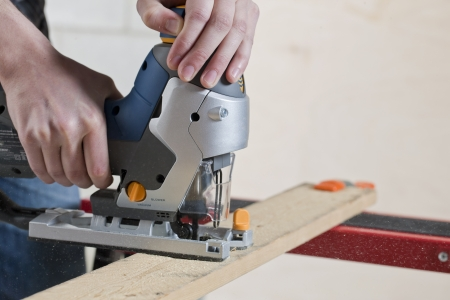wood cutter: Close up image of man cutting a piece of wood