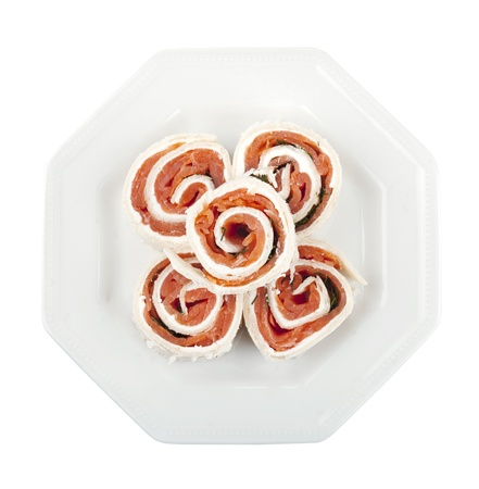 fresh food fish cake: Overhead shot on a plate with smoked salmon rolls against the white background