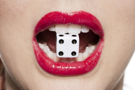 Close-up image of a womans red lips with gambling dice  Stock Photo