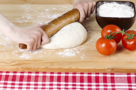 Female hand with rolling pin kneading pizza dough with flour and tomato on the side photo