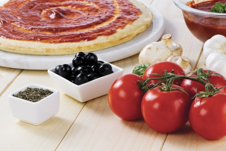 tomato paste: Tomato paste spread on raw pizza dough with tomato, mushrooms, black olives and crushed leaves on the side