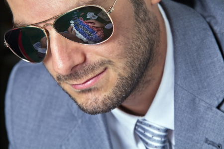 Handsome poker player wearing a shades with poker chips reflection