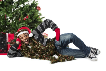 smiing: Portrait of a happy African American man lying on his side beside a Christmas tree, Model  Eddie Reid Stock Photo