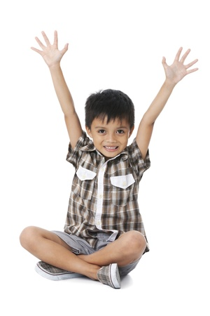 Happy boy sitting cross legged with raised arms on white background Stock Photo - 16193910