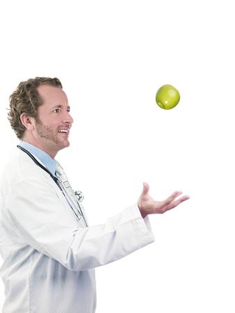 Happy doctor tossing green apple in air against white background, Model  Derek Gerhardt Stock Photo - 17050309