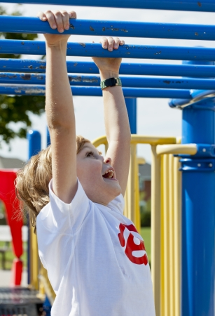 View of a happy elementary boy crossing monkey bar, photo