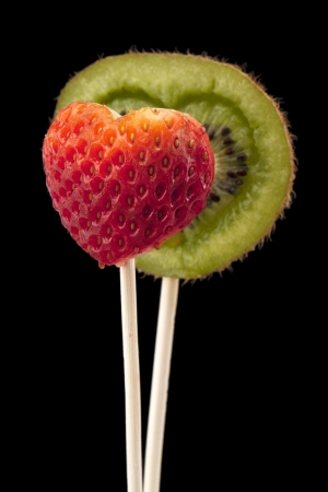 shaped: Close up image of a heart shaped kiwi and strawberry on dark background