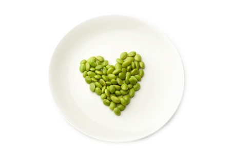 A plate with green beans forming heart on a white background