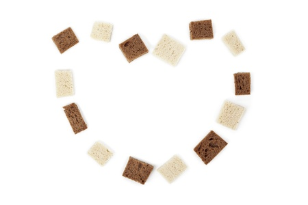 Image of heart shape made of bread cubes against white background