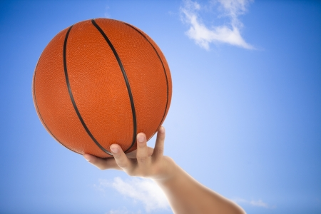 Image of basketball on the hand and sky as background