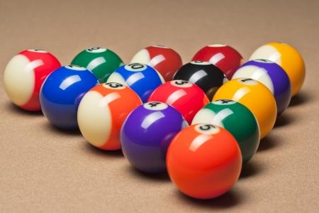 Fifteen billiard spheres lay on brown table