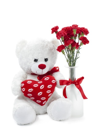 toy bear: Portrait of a flower vase with red flower and a cute stuff toy on the side against the white background