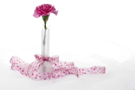lazo rosa: Imagen horizontal de un florero transparente con un clavel rosa atada con un lazo rosa