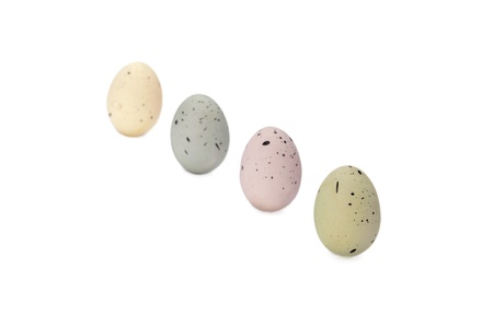 Close up image of four colorful easter eggs against white background
