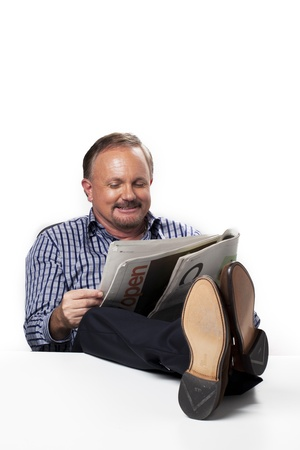 Front view of a businessman reading newspaper while at work, Model  Dan Sanderson Stock Photo - 16225561